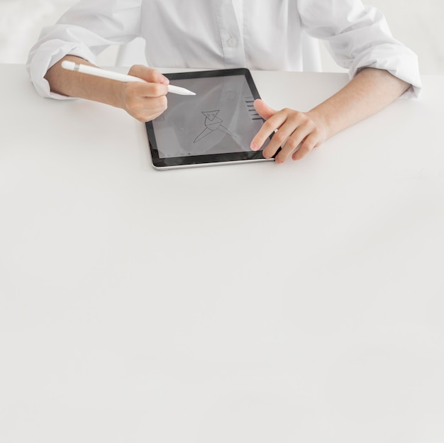 Bambina che studia sulla sua compressa con lo spazio della copia