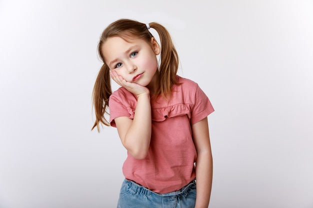 Bambina soffre di mal di denti tenendo la sua guancia