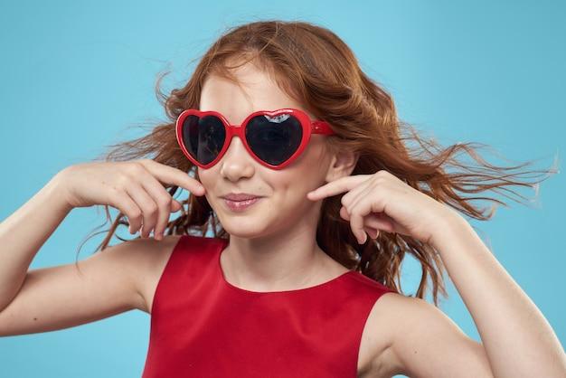 Bambina in occhiali da sole a forma di sfondo blu capelli ricci vestito rosso cuori. foto di alta qualità