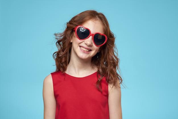 Bambina in occhiali da sole a forma di cuori, vestito rosso e capelli ricci