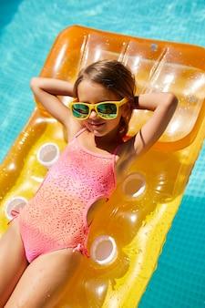 Bambina in occhiali da sole rilassante in piscina, godersi l'abbronzatura