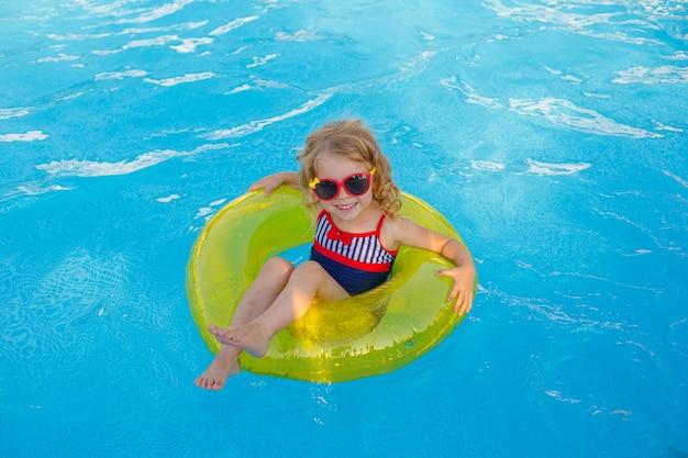 Una bambina in occhiali da sole e un costume da bagno nuota in piscina su un cerchio gonfiabile in estate