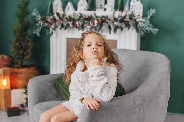La bambina in un maglione si siede sullo sfondo delle decorazioni natalizie.