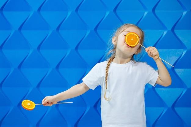 Una bambina con una maglietta sorride e tiene due metà di frutta arancione davanti ai suoi occhi su uno sfondo blu. concept: la lotta all'avitomnosi primaverile.