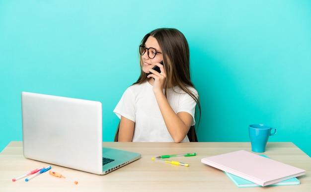 Bambina in un tavolo con un computer portatile su sfondo blu isolato che tiene una conversazione con il telefono cellulare con qualcuno