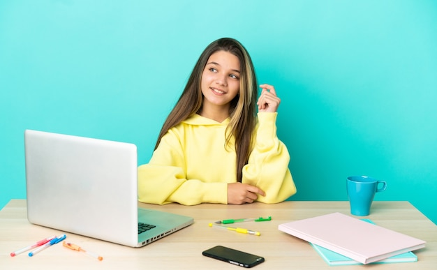 Bambina in un tavolo con un computer portatile su sfondo blu isolato ridendo