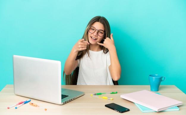 Bambina in un tavolo con un computer portatile su sfondo blu isolato che fa il gesto del telefono e indica la parte anteriore