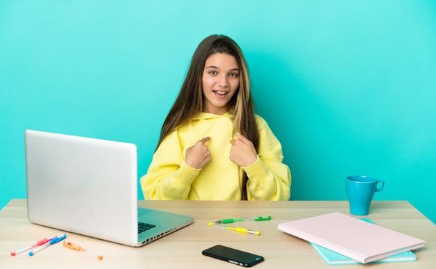 Bambina in un tavolo con un computer portatile su sfondo blu isolato con espressione facciale a sorpresa
