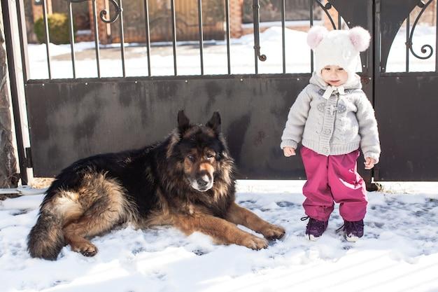 Bambina che parla con il suo cane durante la passeggiata invernale