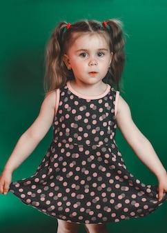 Bambina di tre anni con la coda in abito in posa in studio su sfondo verde 2021