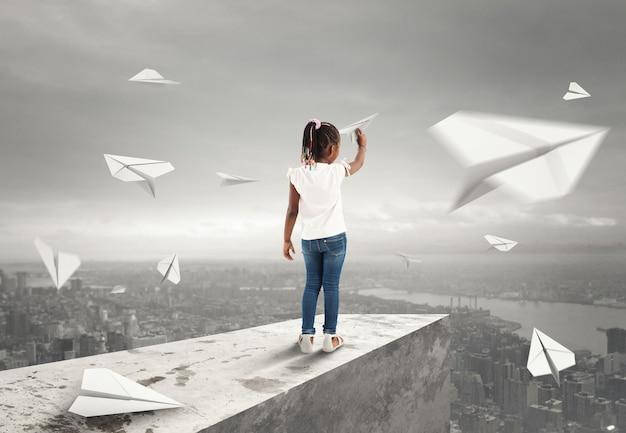 La bambina lancia aeroplani di carta da un tetto sopra la città