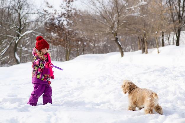 La bambina addestra il suo cane con il giocattolo di porpora dell'anello
