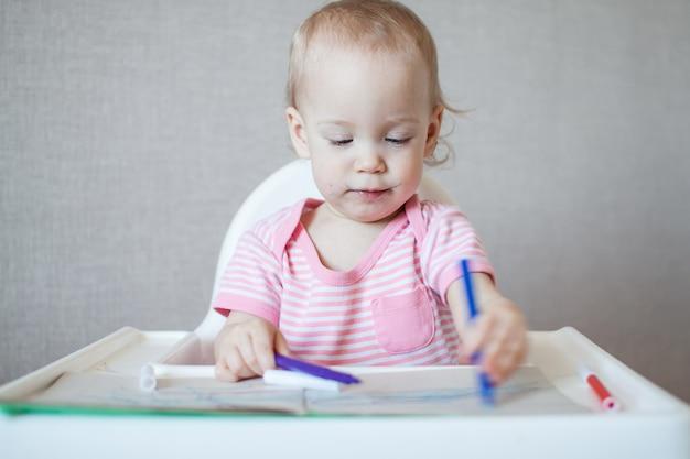 Una bambina cerca di disegnare con pennarelli