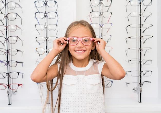 Bambina che prova sugli occhiali presso il negozio di ottica