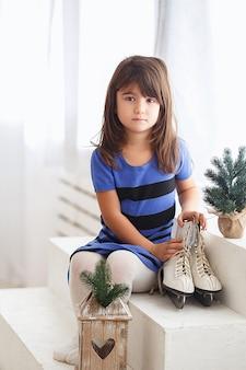 Bambina che prova su un pattinaggio su ghiaccio di grandi dimensioni. ragazzino e pattini
