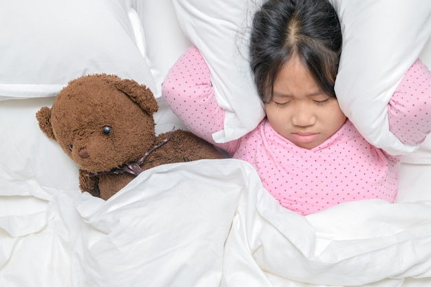 Bambina che cerca di dormire coprendosi le orecchie per evitare il rumore del vicino a casa o in hotel, concetto di problema del rumore