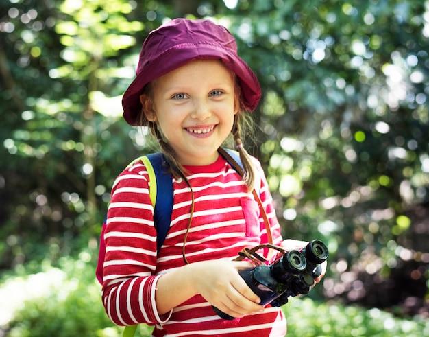 Bambina che utilizza il binocolo nella foresta