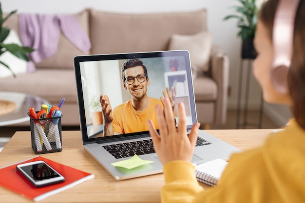 Bambina che utilizza cuffie e laptop per l'apprendimento della classe online dall'insegnante di scuola tramite internet remoto
