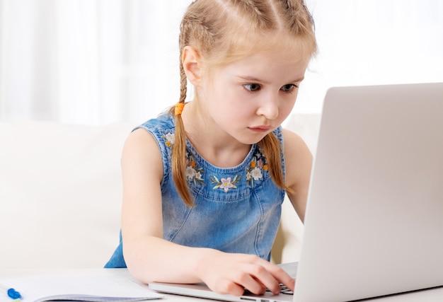Bambina che per mezzo del suo computer portatile