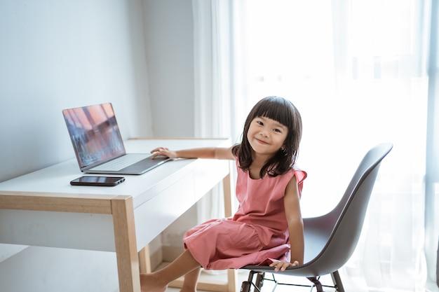 Bambina che per mezzo del computer portatile a casa