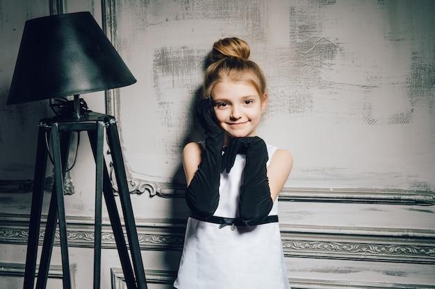 Bambina in un abito vintage. bambino in un elegante abito glamour e guanti. ragazza retrò, modella, bellezza, lampada da terra. retrò, pin up. moda, stile pinup, infanzia.