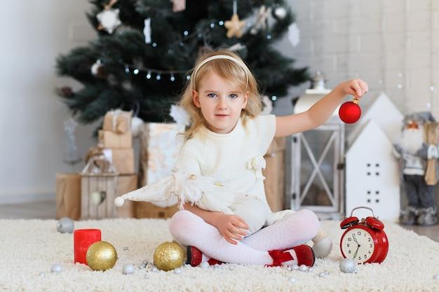 Bambina che aspetta un miracolo nelle decorazioni di natale