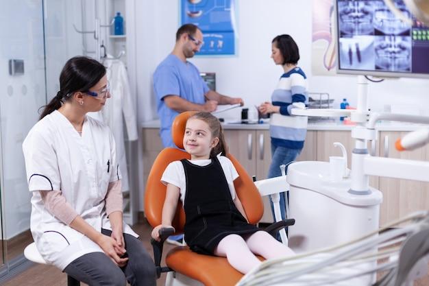 Bambina in attesa di igiene dentale professionale esaminando il medico dentista. bambino con sua madre durante il controllo dei denti con stomatolog seduto su una sedia.