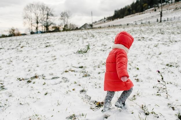 La bambina cammina indietro sulla montagna innevata, natura invernale. bambini, figlia che si godono il viaggio. frost stagione invernale. concetto famiglia felice.