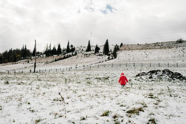La bambina torna a piedi sulla montagna innevata, natura invernale.