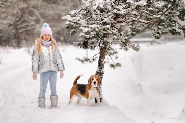 Una bambina in una passeggiata con il suo cane nella foresta invernale. il proprietario e il cane stanno giocando nella foresta innevata