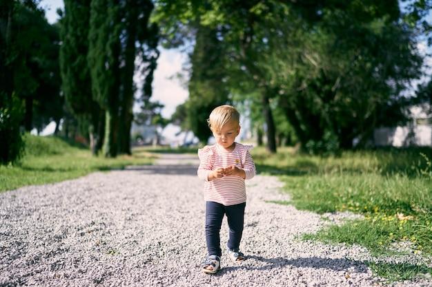 Bambina che cammina lungo un sentiero di ciottoli in un parco verde