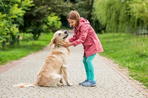 Bambina che cammina con il golden retriever nel parco verde