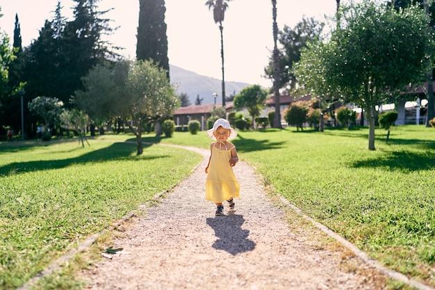 La bambina cammina lungo un sentiero di ghiaia in un parco verde sotto il sole splendente
