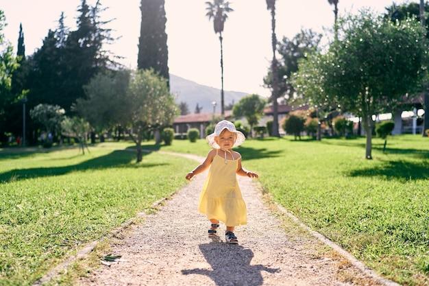La bambina cammina lungo un sentiero di ghiaia in un parco verde
