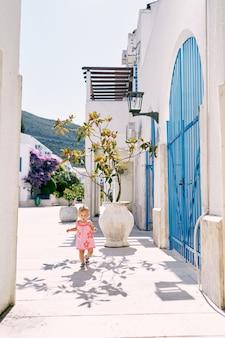 La bambina cammina intorno al cortile della casa davanti a vasche di piante in fiore