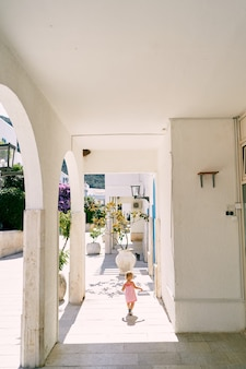 La bambina cammina intorno al cortile della casa oltre le vasche di piante vista posteriore