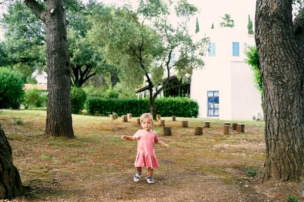 La bambina cammina in una radura vicino a ceppi nel cortile di una casa