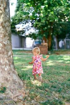 La bambina cammina davanti a un sicomoro in un parco verde