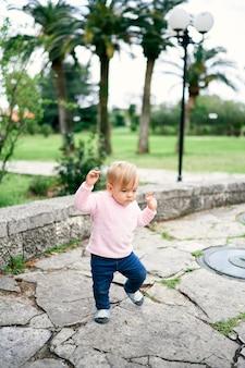 La bambina cammina sulle lastre per pavimentazione sullo sfondo degli alberi