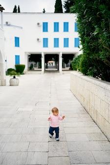 Bambina cammina su lastre di pavimentazione contro un edificio