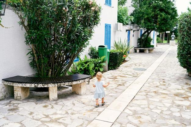 La bambina cammina attraverso il cortile acciottolato vicino alla casa, una panchina e una vista sul retro del verde