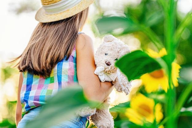 Una bambina cammina in un campo di girasoli e tiene in mano un coniglio di peluche