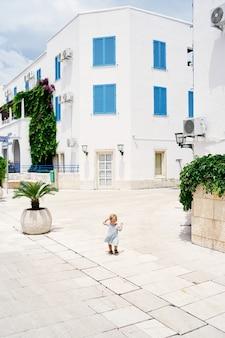 La bambina cammina su una piastrella nel cortile di una casa a tre piani