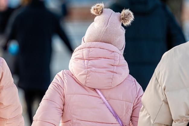 La bambina in una giacca calda e un cappello con nappe è all'aria aperta in una giornata fredda