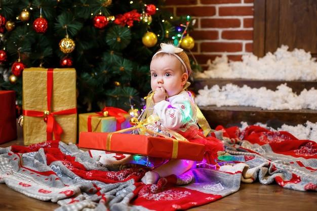 La bambina con un maglione caldo si siede sotto un albero di natale con giocattoli e regali. infanzia felice. atmosfera di festa di capodanno