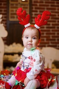 Una bambina con un maglione caldo si siede sotto un albero di natale con giocattoli e regali con le corna in testa. infanzia felice. atmosfera di festa di capodanno