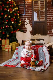 Una bambina con un maglione caldo sta con un albero di natale con giocattoli e regali. buona infanzia atmosfera festosa di capodanno