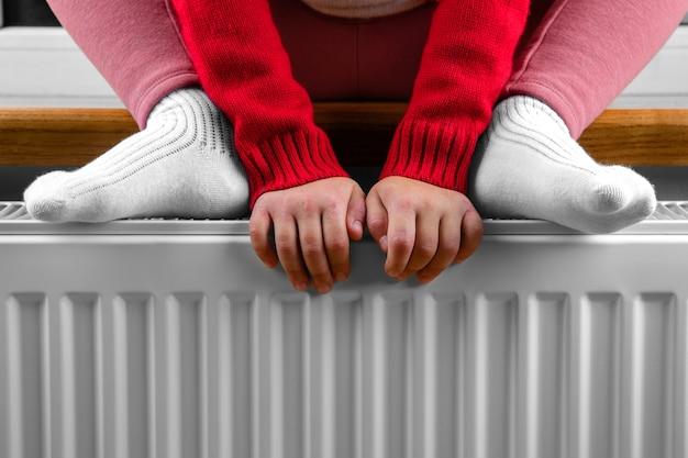 Una bambina si scalda mani e piedi su un termosifone