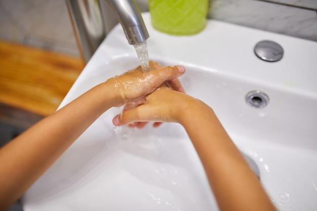 Bambina che si lava le mani con il sapone in bagno