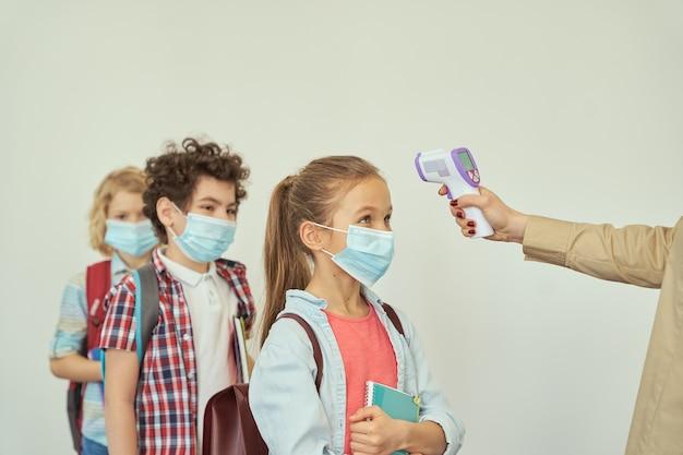 Bambina che guarda il suo insegnante che misura il bambino di screening della temperatura con un termometro digitale mentre